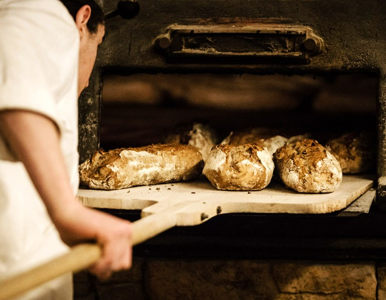 baker putting bread into oven