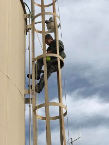 Man on water tower ladder