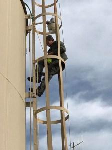 Man on water tower ladder