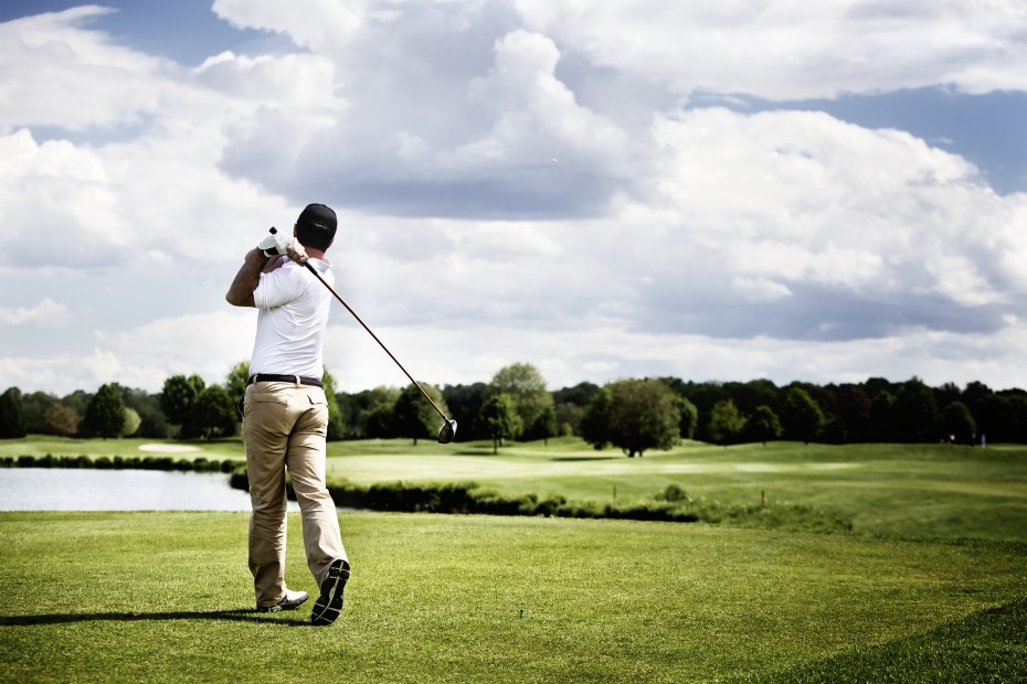 Male golf player teeing off golf ball from tee box