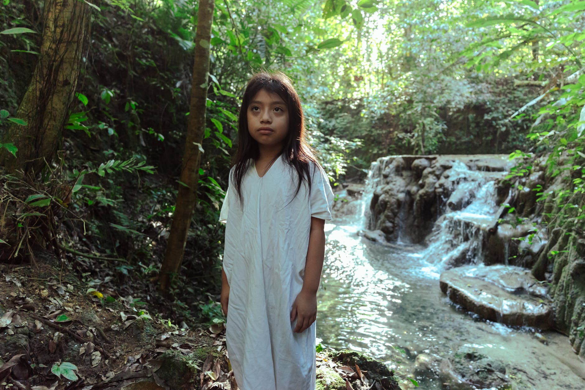 photo of girl standing beside flowing stream