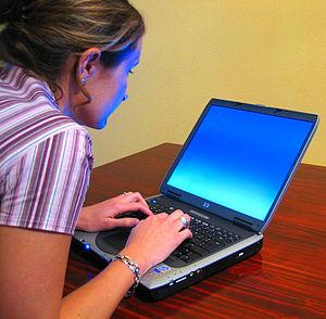 A woman typing on a laptop Français : Une femm...