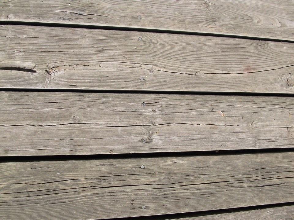 These Unstained wooden planks that look old and rough are not ideal to enhance your deck's appearance.