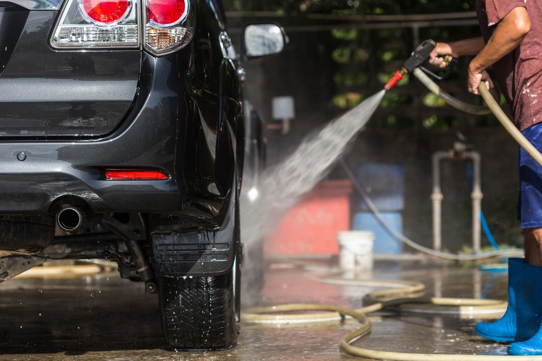 Car maintenance using a pressure washer to wash the car