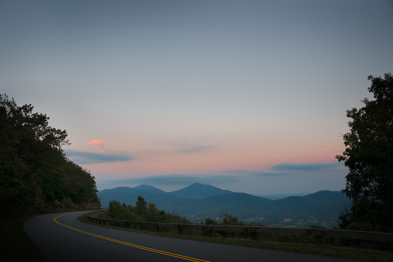 An iconic American Road bends away in the distance with a vista of the Blue Ridge Parkway fills the rest of the frame.
