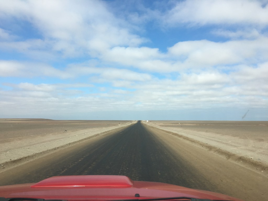 View from the dashboard of our red truck driving down a remote desert road in the Atacama