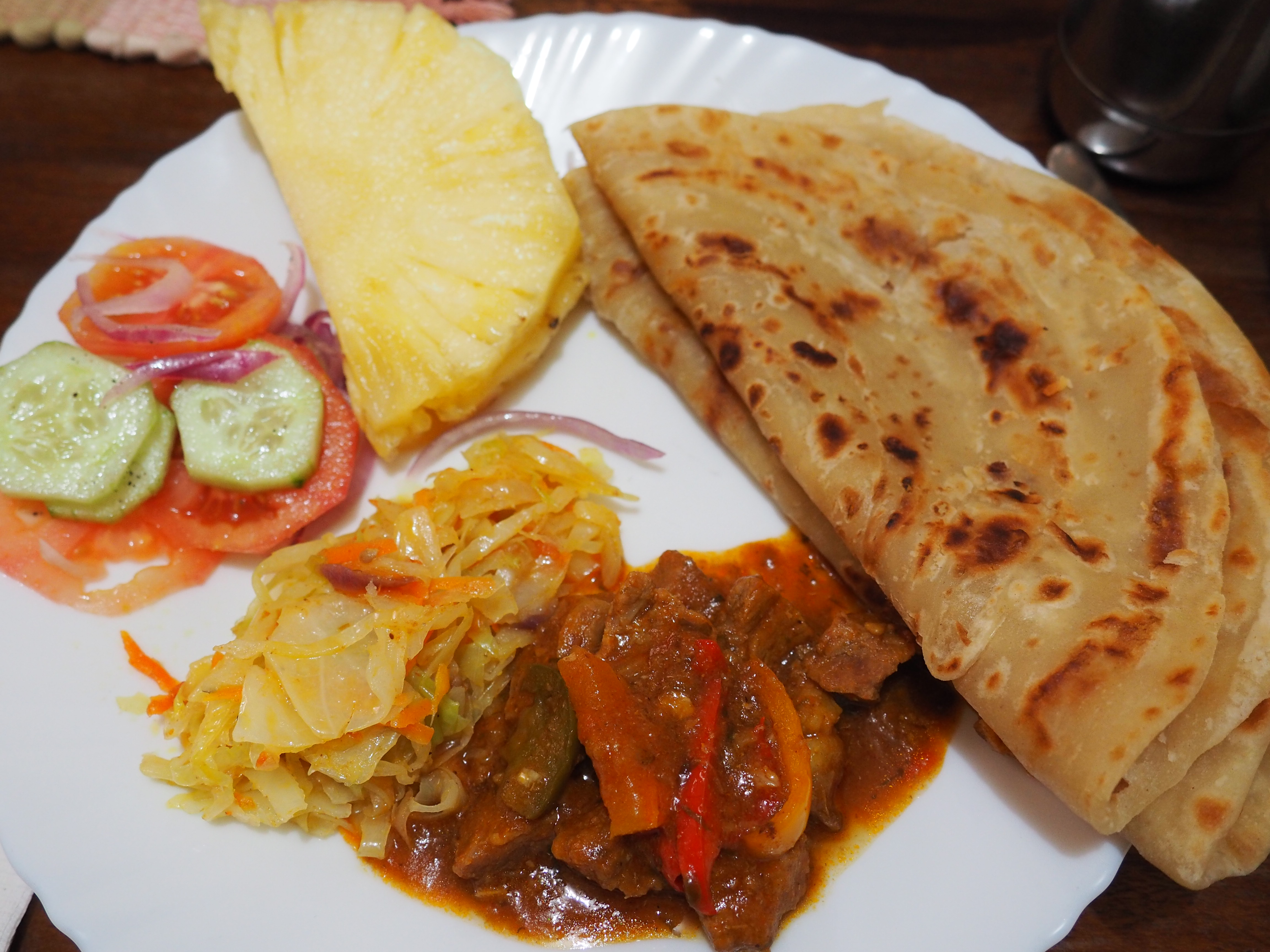 Mama Liz's meal: chapati, beef stew, cabbage, tomato-cucmber salad, and pineapple (Not pictured: amazingly delicious coconut rice)