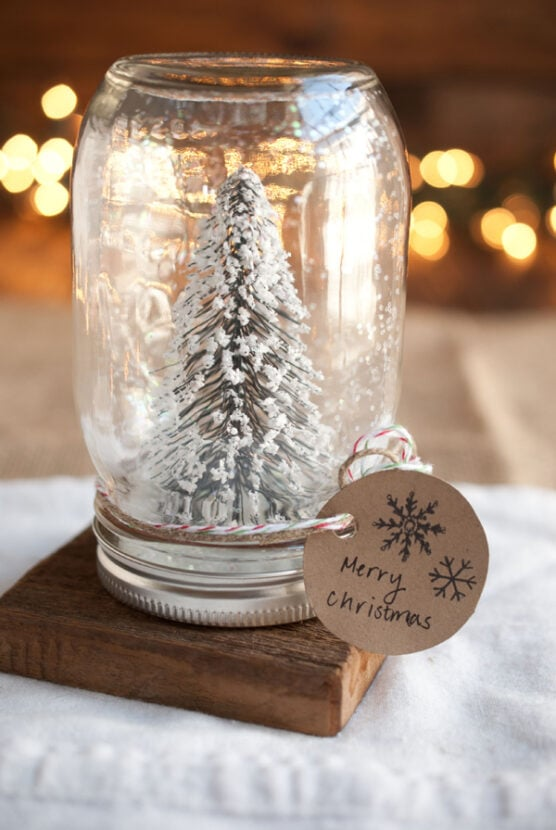 A snowy tree and glitter inside a mason jar