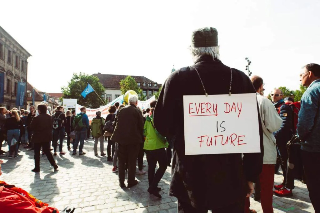 "Man at demonstration wearing a sign that says ""Every day is future""."