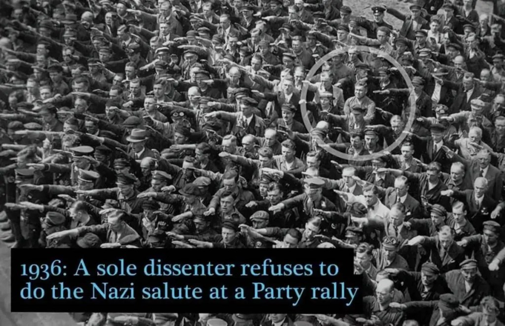 1936: A sole dissenter refuses to do the Nazi salute at a Party rally.