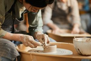 Shaping wet clay on pottery wheel