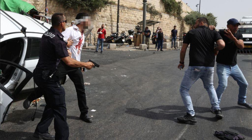 Un officier de police secourt le conducteur d'une voiture à Jérusalem après qu'il ait été attaqué par des manifestants arabes. (Photo : Amit Shabi)