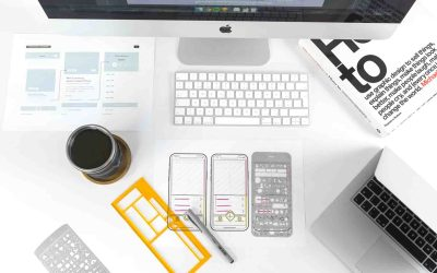 Mobile design plans on a white desk between a laptop and a iMac