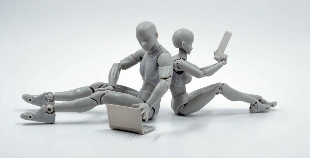 Two robots sitting down next to each other on their laptops and phones