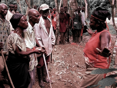 Bad Death Ritual - See the entire post at Ideophone: A bad death ritual in Ghanas Volta Region. On the village cemetery, relatives of a man who died in a hunting accident listen anxiously to a woman who is possessed by the spirit of the deceased. The hunters, who have just brought the spirit home from the place of the accident deep in the jungle, keep their distance. Red is the colour of danger, black that of death.  Photo by Mark Dingemanse