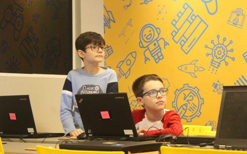 duas crianças prestando atenção na aula de programação