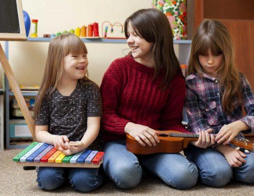prof brincando de musica com duas alunas