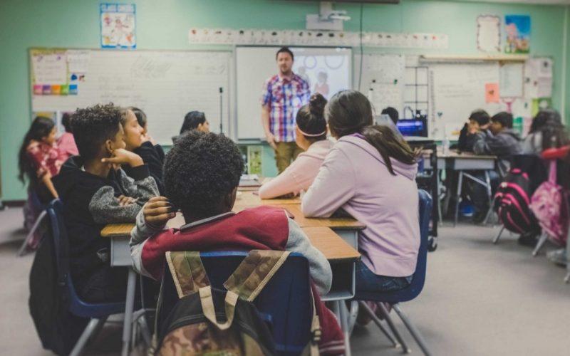 alunos dentro de uma sala de aula prestando atenção no professor