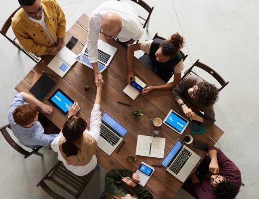 oito pessoas sentadas em volta de uma mesa, cada uma com seu computador