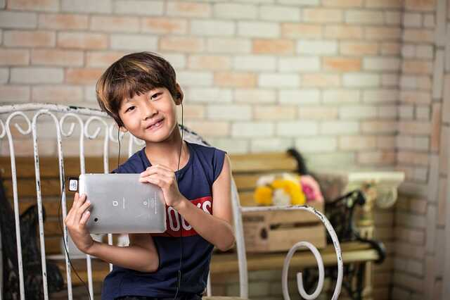 menino feliz brincando com seu tablet