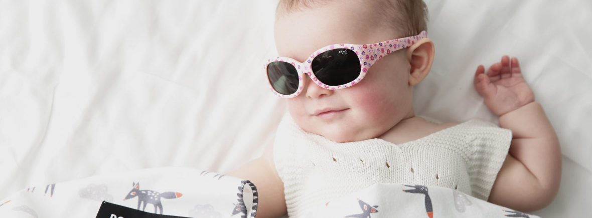 Baby girl wearing IE5630 baby pink with flower print sunglasses, adjustable headband included