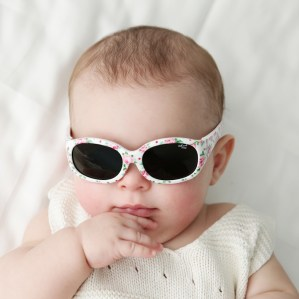 Baby girl wearing Tiny Tots 1 - IE5630 White with rose print sunglasses, adjustable headband included