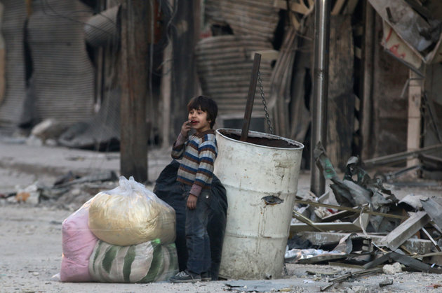A boy stands amid the damage in the rebel-held besieged al-Shaar neighborhood of Aleppo