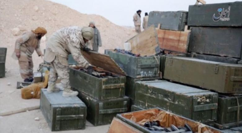 Islamic State fighters search weapon boxes in a Russian base in what is said to be Palmyra
