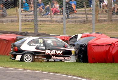 Nankang Tyres BMW Compact Cup competitor Jim Barrett in his E36 Compact 318TI make contact with the tyre wall at Quarry Corner on Sunday. https://idrismartin.wordpress.com/