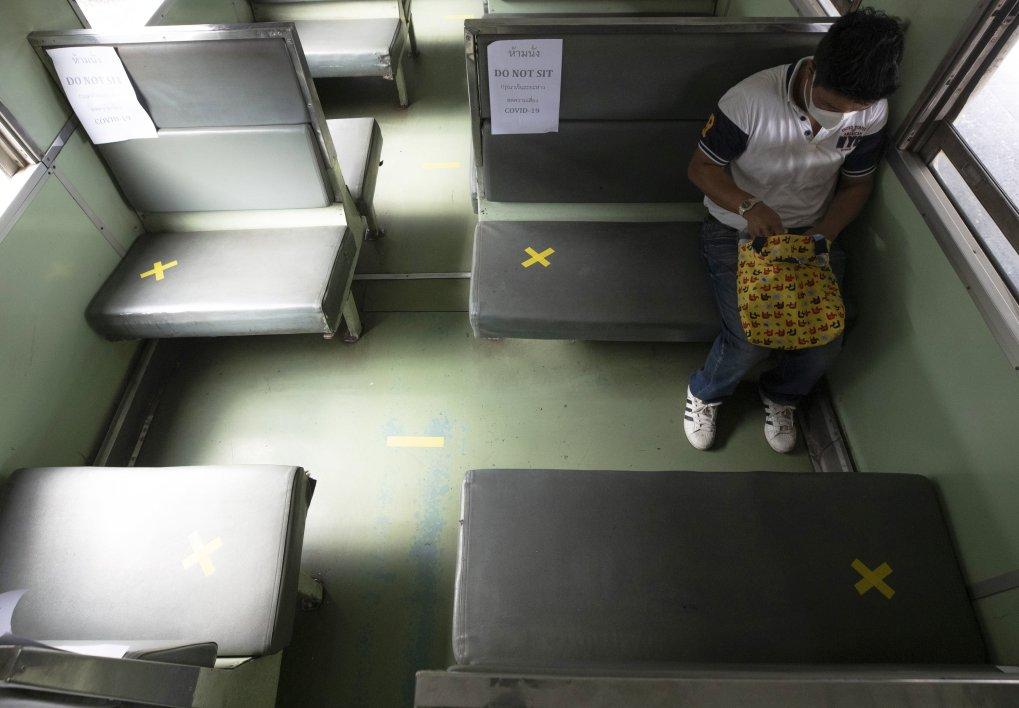 Un passager est assis seul dans un wagon de train avec des sièges décalés portant un masque protecteur à la gare de Hua Lamphong à Bangkok, en Thaïlande, le mercredi 1er avril 2020 (AP Photo)