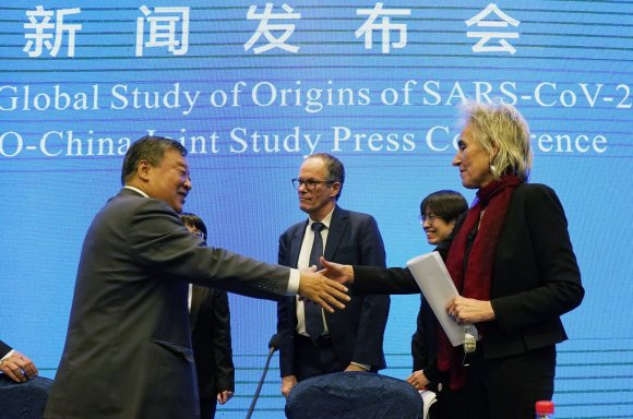 Marion Koopmans (R) and Peter Ben Embarek (C) of the World Health Organization team say farewell to their Chinese counterpart Liang Wannian after a WHO-China Joint Study Press Conference at the end of the WHO mission in Wuhan, China, Feb. 9, 2021. (AP Photo)