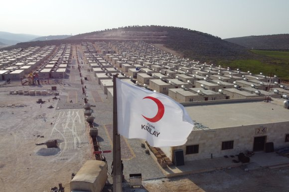 A Turkish Red Crescent (Kızılay) flag waves over houses built by Kızılay for displaced Syrians in Sarmada, Idlib province, Syria, April 3, 2021. (AA Photo)