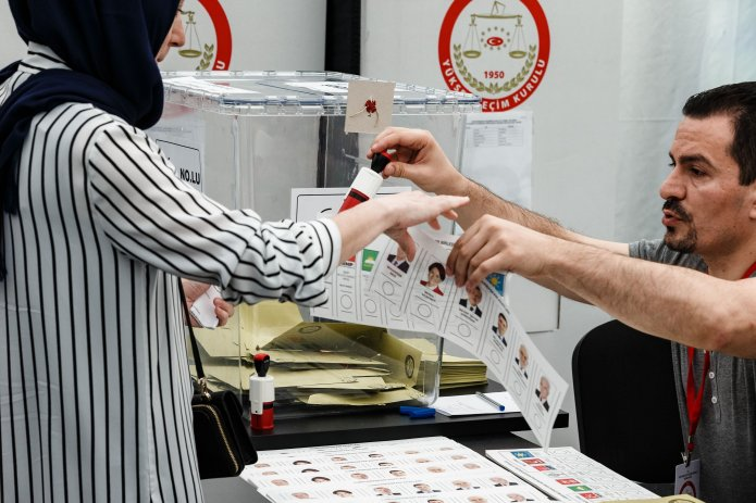 A member of the electoral commission gives a Turkish woman ballot paper and the stamp to mark her candidates, Hamburg, June 7, 2018. (Getty Images)