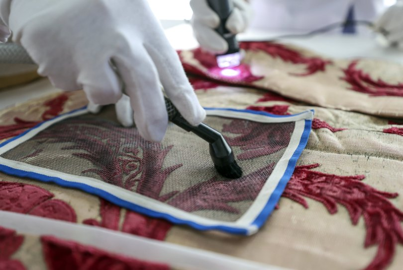 A close-up of a hand of a restorer while working on Sultan Suleiman I