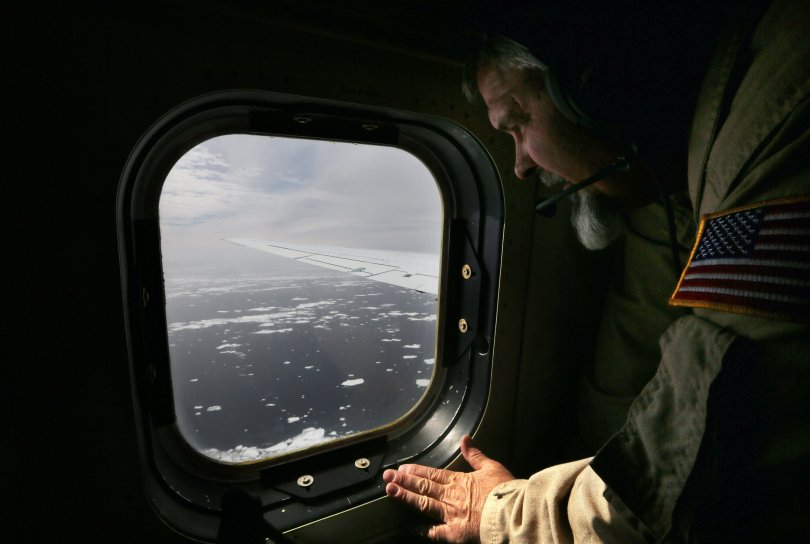Lyn Lohberger of NASA looks out as sea ice floats near the coast of West Antarctica from a window of a NASA Operation IceBridge airplane on October 27, 2016 in-flight over Antarctica. (Getty Images)