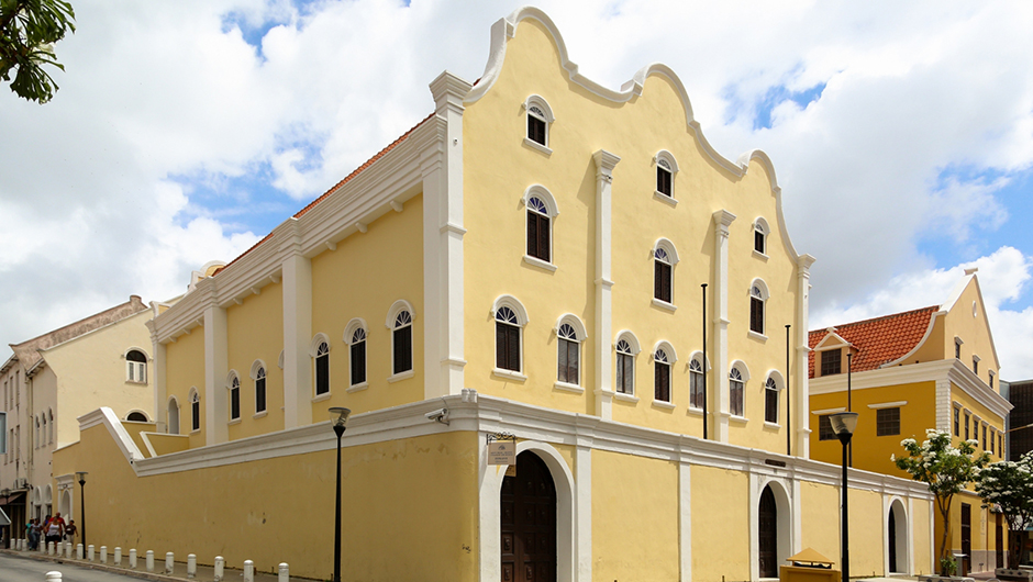 Mikve Israel Emanuel Synagogue Willemstad Curacao yellow 3-story building with white trim and ornate undulating roofline frontispiece