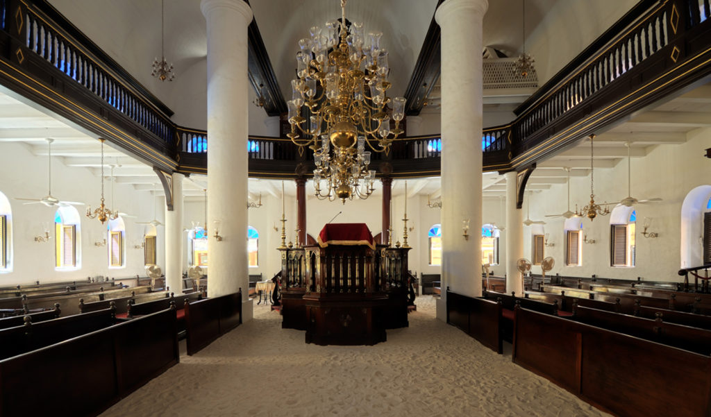 Opened in 1732, the sanctuary of the Mikvé Israel-Emanuel Synagogue in Willemstad, Curaçao, still has its original mahogany furniture, candle chandeliers, and sand-covered floors