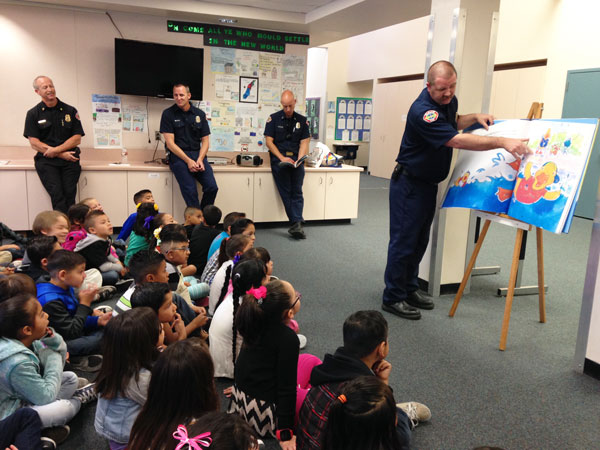 iecn photos/yazmin alvarez Matt Payne, Rialto firefighter paramedic, leads a sing-a-long with first graders teaching them all about water safety through the program, Stewie the Duck Learns to Swim.