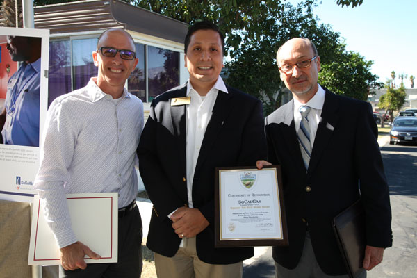 Photo Courtesy/SoCalGas (Center) Dan Flores, chief of staff for Supervisor Josie Gonzales, San Bernardino County Board of Supervisors, District 5, presents a certificate of recognition to David Buczkowski (left) and Joe Velasquez, SoCalGas executives, during a ribbon-cutting ceremony at Mt. Slover Trailer Village in Colton, Nov. 6, 2015. SoCalGas is the first utility in the state to completely convert a mobile home park's privately-owned natural gas distribution system to a brand new and advanced distribution system under the three-year statewide Mobilehome Park Utility Upgrade Pilot Program.
