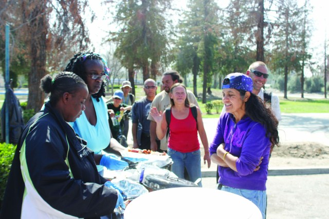 Photo/Anthony Victoria: Myesha Johnson, left, and Vanetta Morris, right, both of San Bernardino helping feed homeless residents at Seccombe Lake Park on February 27.