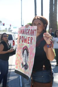 "Photo/Anthony Victoria: Immigrant rights advocate Erika Paz showing solidarity by holding a sign that reads, ""Immigrant Power."""