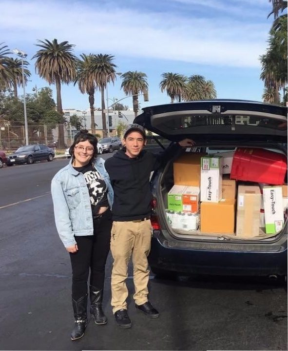two people standing next to open hatchback car filled with boxes
