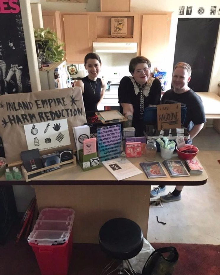 three volunteers standing behind a table of literature and supplies