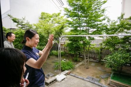 カメのいる裏庭。寛子さんがへばりつくニホンイシガメを説明してくれてます。