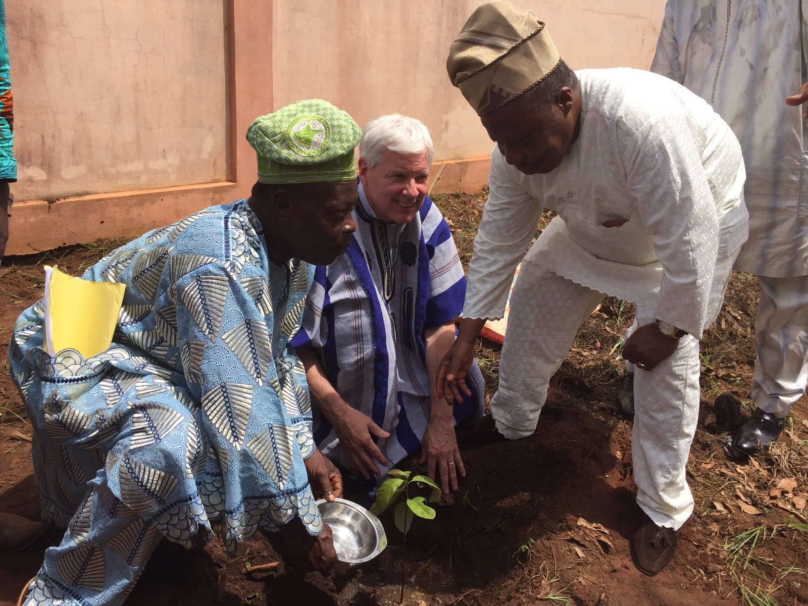 IFDC President and CEO J. Scott Angle and the Honorable Pierre Adechi, Mayor of the city, plant a tree outside the town hall.