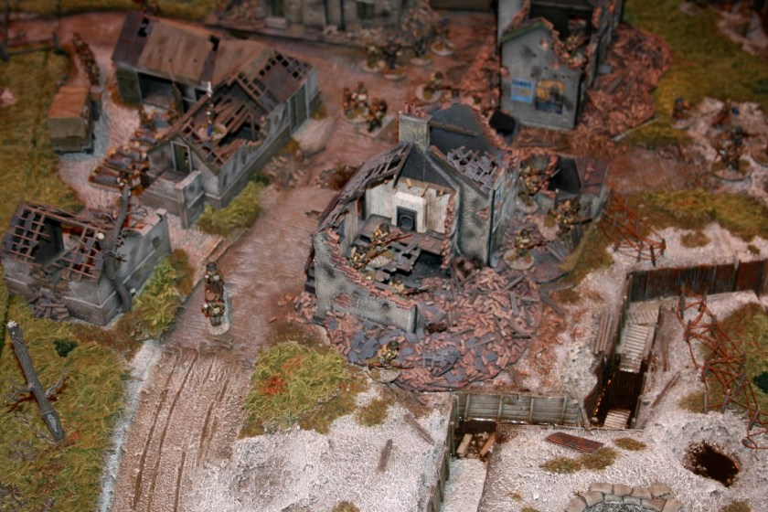 British Infantry advance through the ruins of a French village.