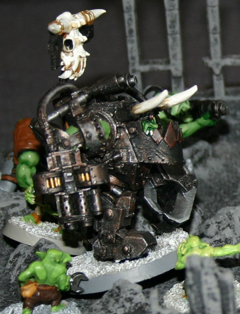 Ork Warboss in Mega-Armour from Felix's collection in the ruins of an Imperial City with Grot helpers.