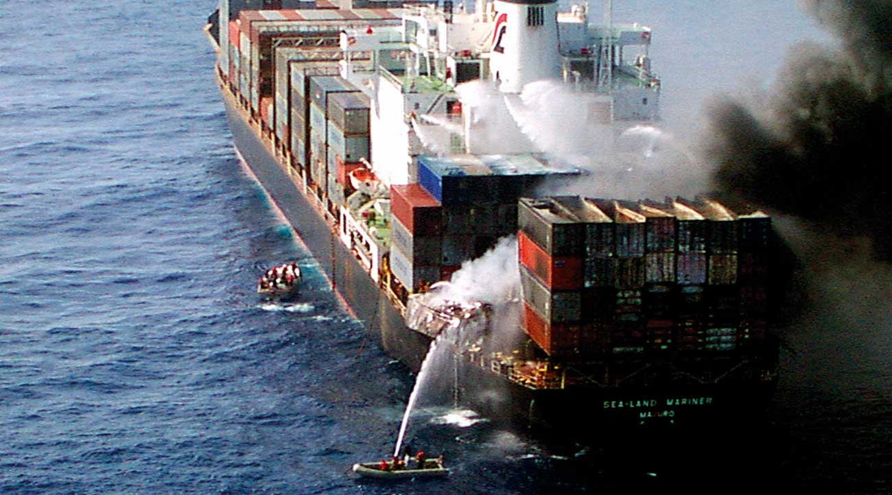 Water streams from boats and on board pour water on the fire burning in containers on the Sea Elegance.