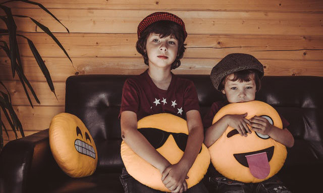 Two kids on couch with fun pillows