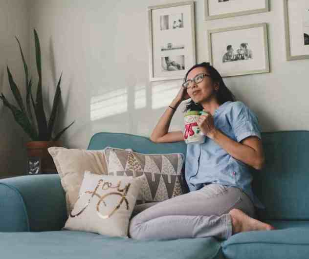 Woman on couch with inspirational pillow decor